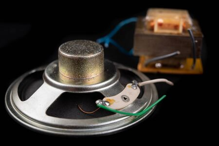 Old speaker removed from the radio. Electronics from old electronic devices. Dark background.