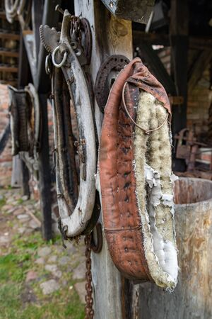 Harness for a horse in an old stable. Old equestrian accessories. Place - stable. Stock Photo