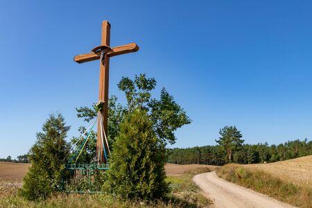 A roadside wooden cross in Central Europe. Christian cross standing by a dirt road. Summer season.