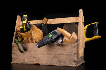 Old wooden tool box. Various DIY accessories on a workbench. Dark background.