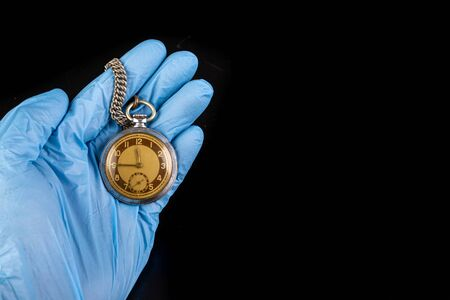 Old analog watch on a latex glove. Hand of a medical worker in a glove with a watch on his hand. Dark background. Standard-Bild - 129392585
