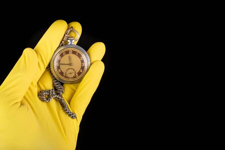 Old analog watch on a latex glove. Hand of a medical worker in a glove with a watch on his hand. Dark background. Standard-Bild - 129392586