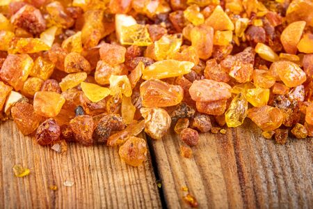 Small raw amber on a wooden table. A precious find from the coast of Central Europe. Light background. Standard-Bild - 129392783