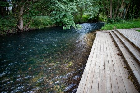 A wooden jetty at a rushing river. marina for canoeists in Central Europe. Summer season. Banco de Imagens