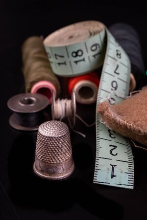 Old sewing accessories on the black table. Shears, threads and tape measure for working as a seamstress. Dark background.