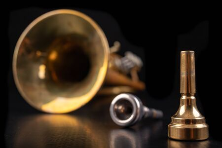 Mouthpiece and trumpet covered with patina on a dark table. Accessories for musicians ready to use. Black background.