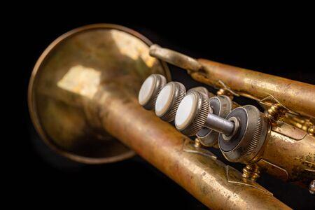 Mit Patina überzogene Trompete auf einem dunklen Tisch. Vernachlässigtes Musikinstrument. Schwarzer Hintergrund. Standard-Bild