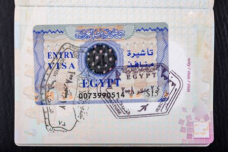Visa to Egypt in the passport. Documents needed to cross the border. Dark background.