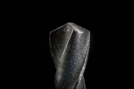 Metal drill bit. Magnifying tools for metalworking. Dark background.