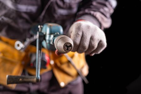 Production worker with tool belt. Drill in the hand of an employee. Dark background. 写真素材
