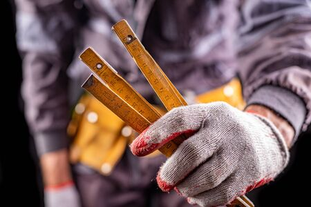 Production worker with tool belt. A measuring tape in the hand of a worker. Dark background. 写真素材