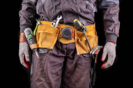 Production worker with tool belt. Screwdriver in worker kekek. Dark background.