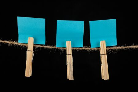 Wooden buckles hung on a clothesline and colored cards. Place on the cards for text messages. Dark background.