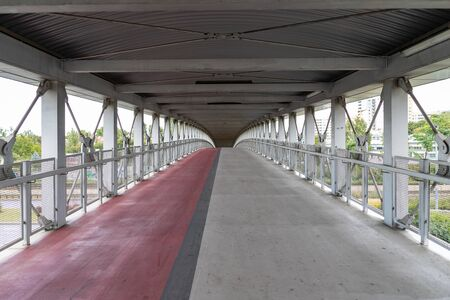 A wide covered pedestrian bridge in the city. A road for people and cyclists. Autumn season.