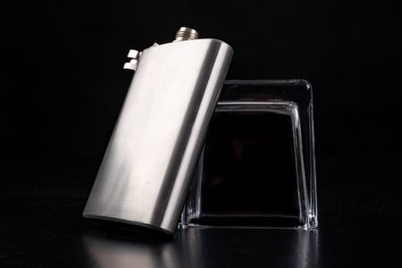 Metal shaker, hip flask and inverted vodka glass. Bartender accessories on the table. Black background.