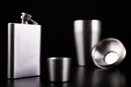 Hip flask and stainless steel shaker. Bartender accessories on the table. Black background. Stok Fotoğraf