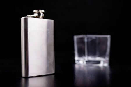 Hip flask and a glass of thick glass for vodka. Bartender accessories on the table. Black background.
