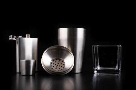 Metal shaker, hip flask and vodka glass. Bartender accessories on the table. Black background.