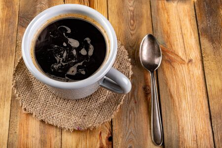Black coffee in a gray mug and a teaspoon on a wooden table. Tasty stimulant drink. Dark background. Reklamní fotografie