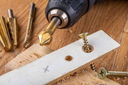 Taper drill and countersink for workshop salts. Accessories and tools in the workshop. Light background. Stock Photo
