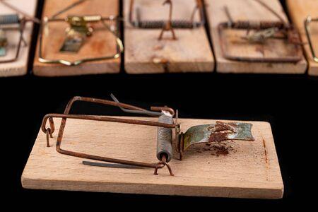 Patas de ratón viejo sobre una mesa oscura. Accesorios para la captura de pequeños roedores en el hogar. Fondo negro. Foto de archivo