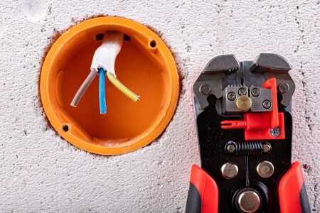 Socket in a raw wall with electric wires and electric insulation stripper. Repair of the electrical installation in the household. Light background.
