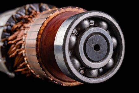 Ball bearing on the motor rotor. Copper motor winding. Dark background.