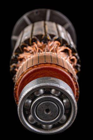 Ball bearing on the motor rotor. Copper motor winding. Dark background.