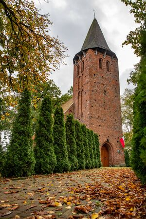 A small church built of red brick. Christian Temple in Central Europe. Autumn season.