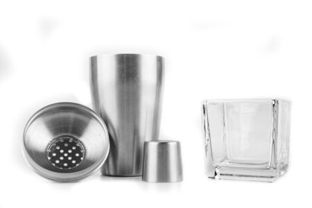 Shaker and bartending accessories on a white table. Mixing different alcohols to prepare drinks. Light background.