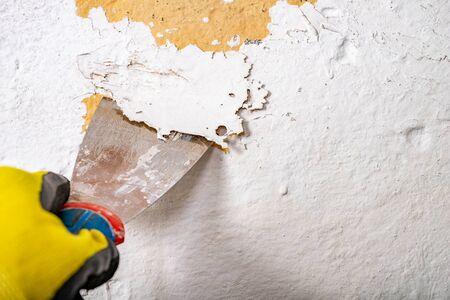 Alte Farbe mit einem Metallspachtel von der Wand entfernen. Kleine Malerarbeiten zu Hause. Heller Hintergrund. Standard-Bild