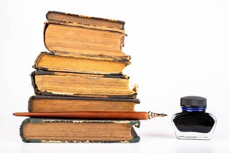 Old dusty books and writing nib on a bright countertop. Library items in old bindings. White background.