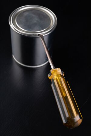 Opening a paint can with a screwdriver. An open can with new paint. Dark background.
