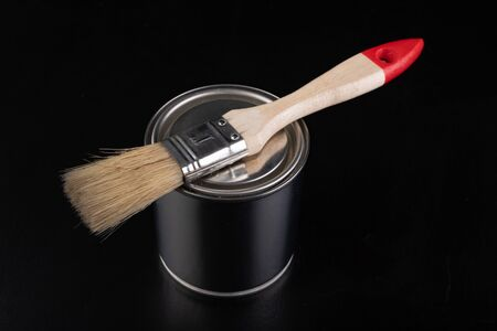 Closed metal can with paint and paintbrush. Painting accessories on a workshop table. Dark background. 写真素材