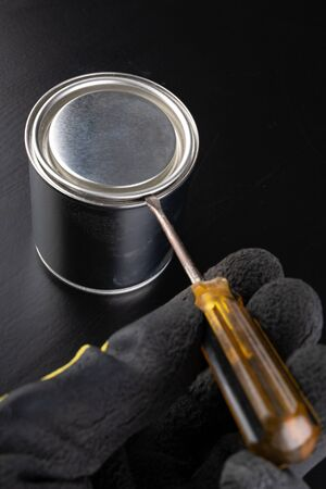 Opening a paint can with a screwdriver. An open can with new paint. Dark background. Standard-Bild
