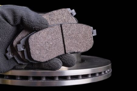 Brake pad for a passenger car in the hand of a mechanic. New spare parts for car repairs. Dark background.