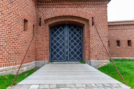 Old historic gate in a brick building. Old building with old doors. Autumn season.