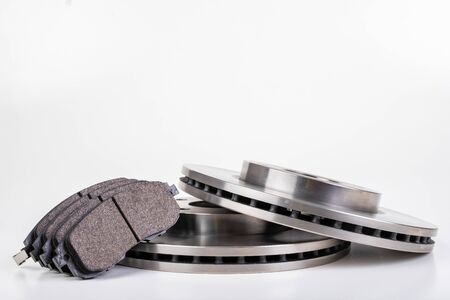 Steel brake discs and brake pads for a passenger car. New spare parts for car repairs. White background. Reklamní fotografie