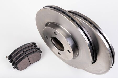 Steel brake discs and brake pads for a passenger car. New spare parts for car repairs. White background. Stock Photo