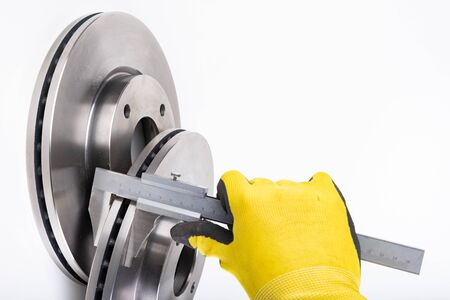 Measuring brake discs with a caliper. Car parts workshop measurements. Light background. Banque d'images