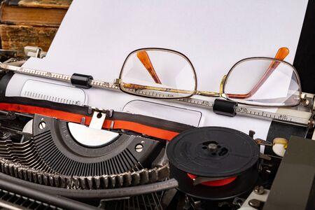 Typewriter and old books. Writer's place of work. Dark background.