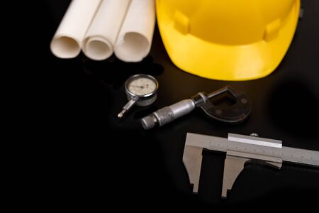 Measuring instruments, helmet and documents. Accessories for an engineer on a construction site. Dark background. Archivio Fotografico