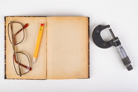 Micrometer and old book with glasses on a white table. Workshop accessories. Light background.