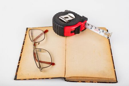 Measuring cup and old book with glasses. Accessories for measurements in carpentry. Light background.