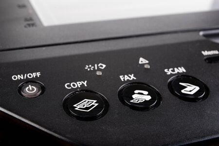 Control buttons on the printer. Control panel in photocopier. Dark background.