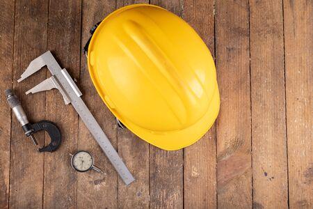 Casco protettivo e strumenti di misurazione. Accessori da lavoro per addetti alla produzione e ingegneri. Sfondo scuro. Archivio Fotografico