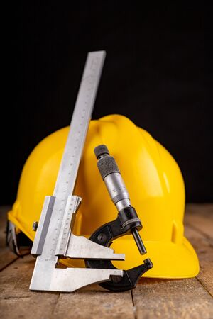 Protective helmet and measuring tools. Work accessories for production workers and engineers. Dark background.