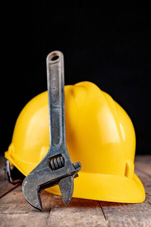Protective helmet and wrench. Work accessories for production workers. Dark background.