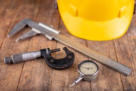 Casco protettivo e strumenti di misurazione. Accessori da lavoro per addetti alla produzione e ingegneri. Sfondo scuro.