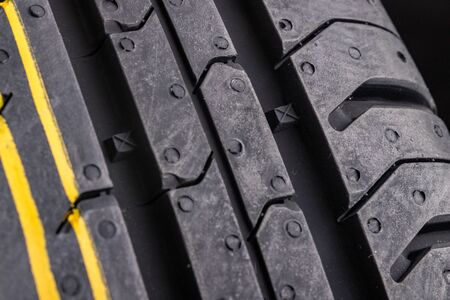 The tread of a new car tire. Car accessories. Dark background. Stock fotó